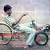 An associate tries out a modified bicycle design built by Ray Wijewardene to improve speed and reduce effort for the rider. Circa 1985.